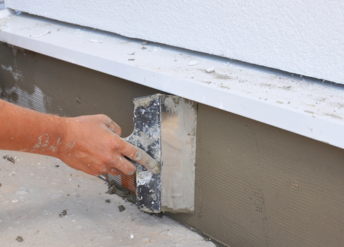 Picture of man's hand installing plaster to repair cracks in the foundation for customer in Syracuse, NY